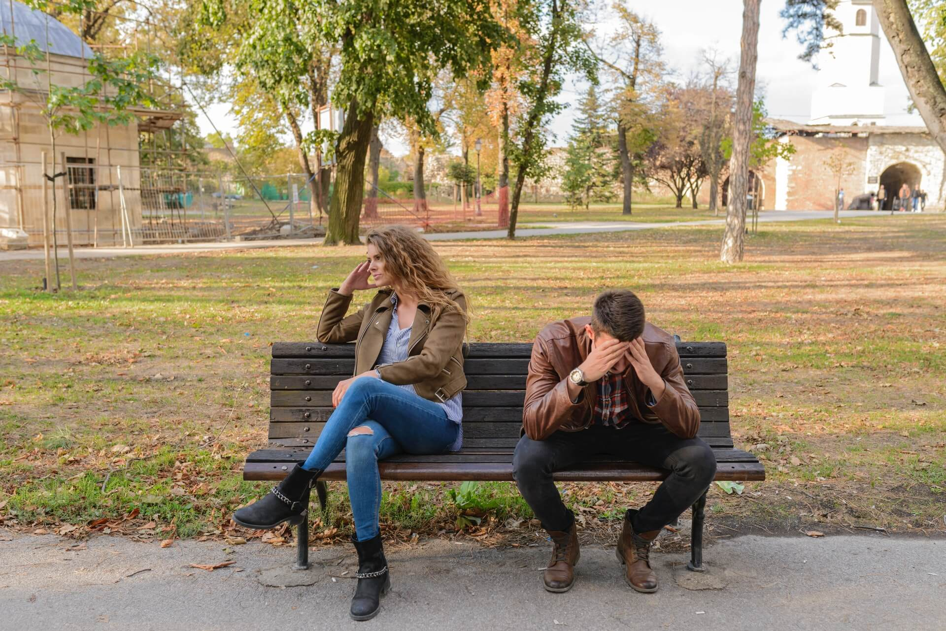 unhappy couple sitting on bench arguing