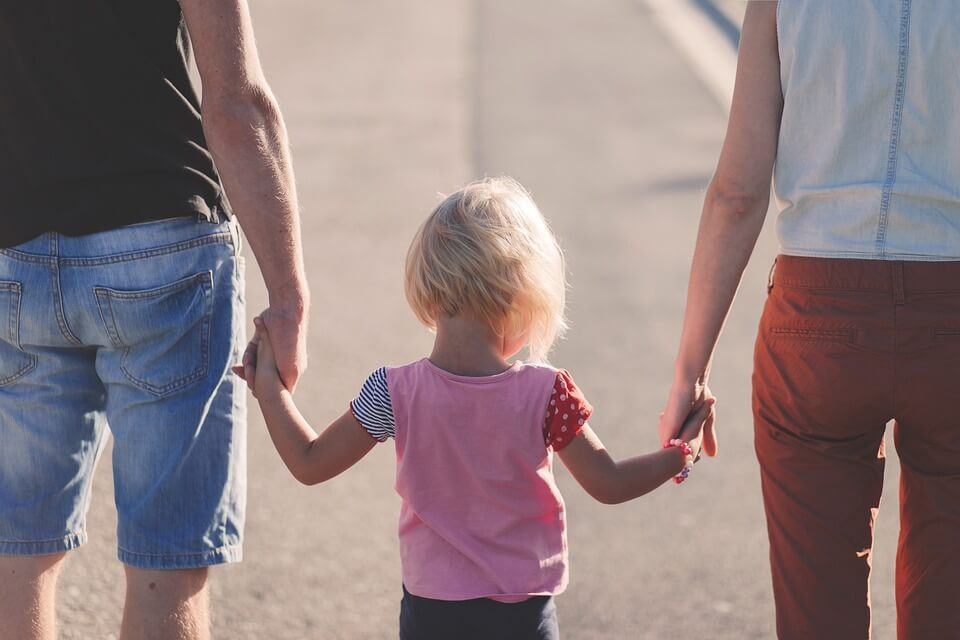 young girl holding hands with parents